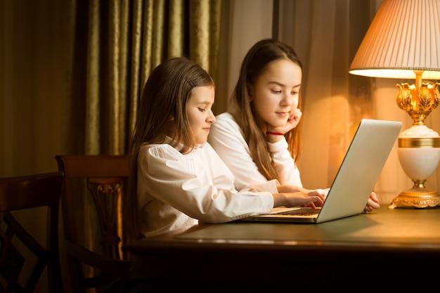 Nette mädchen, die am tisch sitzen und laptop benutzen