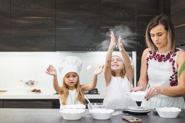 Nette mädchen, die in der küche genießen, während mutter lebensmittel zubereitet
