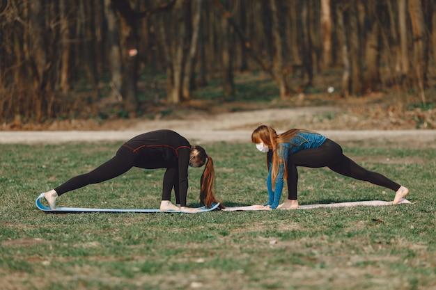 Nette mädchen, die yoga in einer maske tun