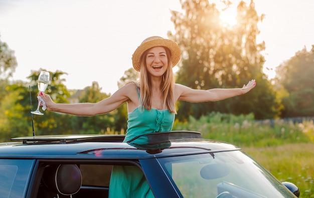 Nette mädchenfrau freut sich mit einem glas wein lehnend aus der luke des autos an einer party im sommer in der natur heraus.