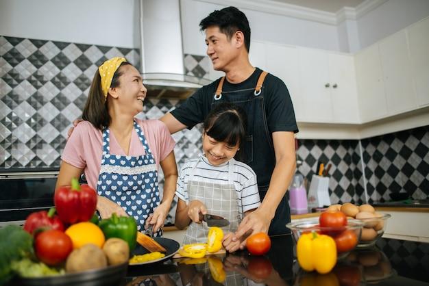 Nette mädchenhilfe, die ihre eltern gemüse schneiden und beim zusammen kochen in der küche lächeln