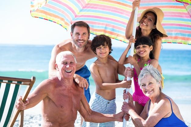 Nette mehrgenerationenfamilie, die ihren regenschirm aufstellt