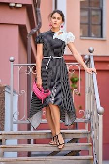 Nette moderne dame im langen gestreiften kleid, welches die treppe absteigt