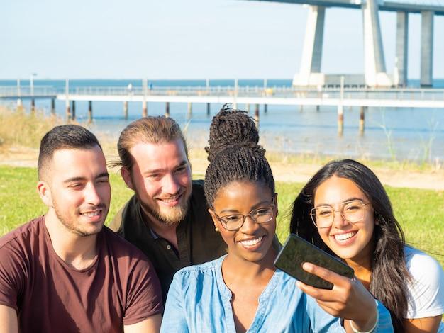 Nette multiethnische leute, die das selfie im freien nehmen
