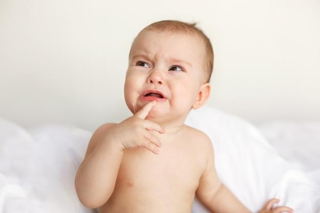 Nette nette kleine babyfrau, die weint und mit ihrer mutter zu hause auf dem bett liegt.