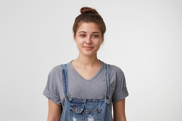 Nette nette und attraktive junge frau sieht umgänglich mit einem leichten lächeln aus, das insgesamt in jeans gekleidet ist