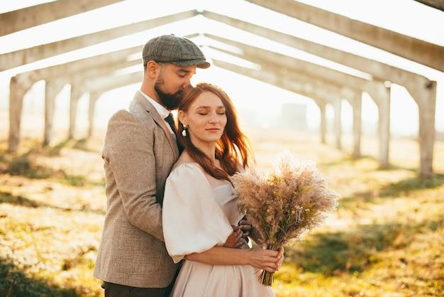 Nette neue familie gerade verheiratetes paar, das im sonnenlicht umarmt