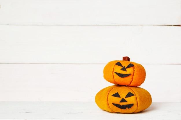 Nette orange handgemachte filzkürbise halloweens auf einem alten weißen hölzernen mit kopienraum
