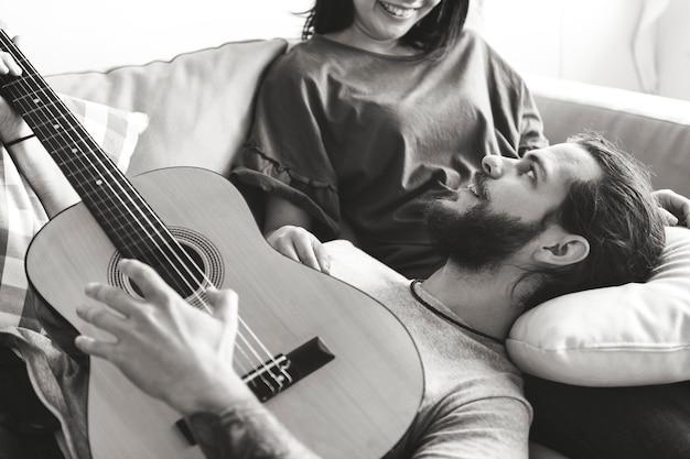 Nette paare auf einem couchfreund, der ein gitarrenmusik- und -liebeskonzept spielt