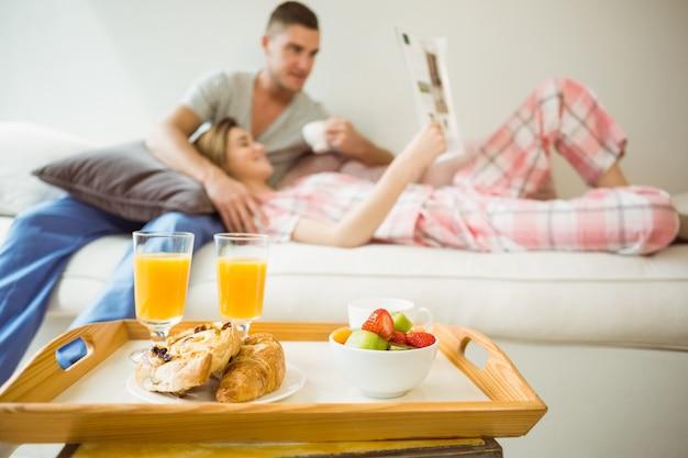Nette paare, die auf couch am frühstück sich entspannen