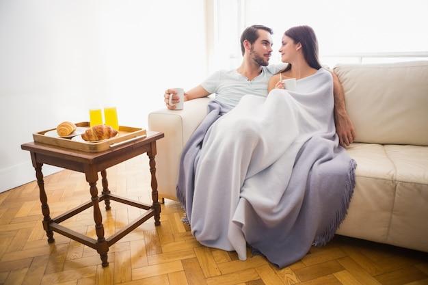 Nette paare, die auf couch unter decke sich entspannen
