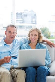 Nette paare, die auf ihrer couch unter verwendung des laptops sitzen, um online zu kaufen