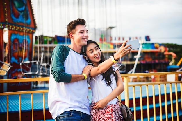 Nette paare, die ein selfie an einem vergnügungspark nehmen