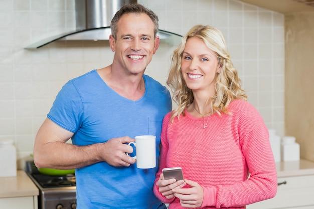 Nette paare, die kaffee trinken und smartphone in der küche betrachten