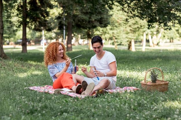 Nette paare, die mit blasen am picknick spielen