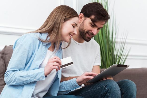 Nette paare, die schauen, um onlineprodukte zu kaufen