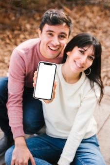 Nette paare, die smartphoneschirm zeigend umarmen
