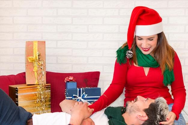 Nette paare in der liebe, die zu hause weihnachten, mit geschenken feiert
