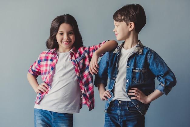 Nette paare von kindern in der zufälligen kleidung werfen auf und lächeln
