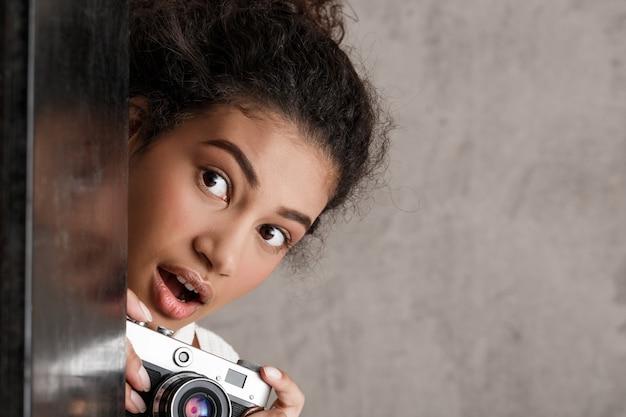 Nette paparazzi der frau, die heimlich fotos von der ecke machen