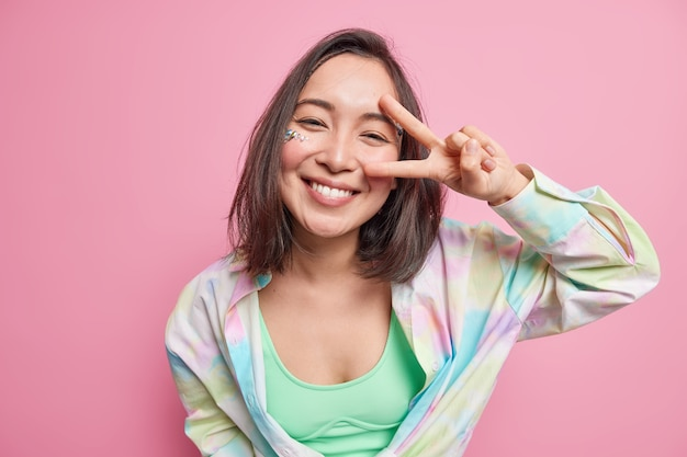 Nette positive asiatische frau mit dunklen haaren zeigt v zeichen friedensgeste sieht glücklich aus in lässigem hemd gekleidet genießt guten tag isoliert über rosa wand drückt unbeschwerte gefühle aus.