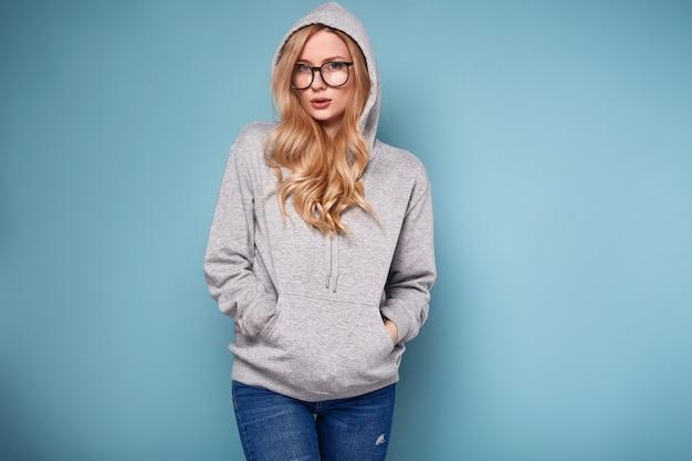 Nette positive blondine im grauen hoodie und in den gläsern