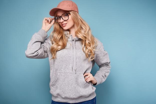 Nette positive blondine in einer rosa baseballmütze