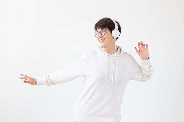 Nette positive frau mittleren alters in pullover und brille hört musik mit drahtkopfhörern