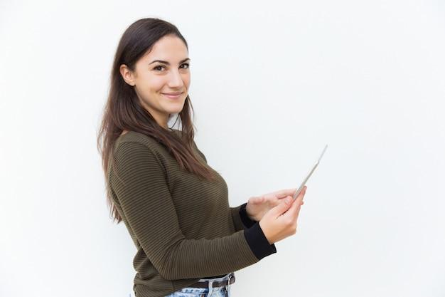 Nette positive lateinische frau, die auf tablette online erhält