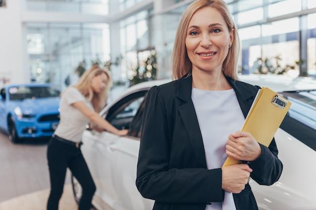 Nette reife autoverkäuferin, die zur kamera vor neuem automobil lächelt.