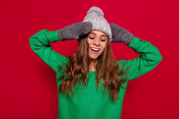 Nette reizende glückliche frau mit gekleidetem wintermütze des langen haares und grünem pullover, der über rotem hintergrund mit geschlossenen augen, glücklichem lächeln und ruhigen gefühlen steht