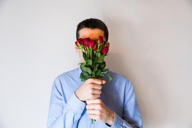 Nette, romantische valentinstagüberraschung, rosafarbener blumenstrauß des gutaussehenden mannes, versteckend hinter blumen