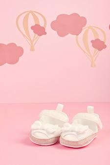 Nette rosa schuhe des babys über dem rosa pastellhintergrund mit wolken und ballons