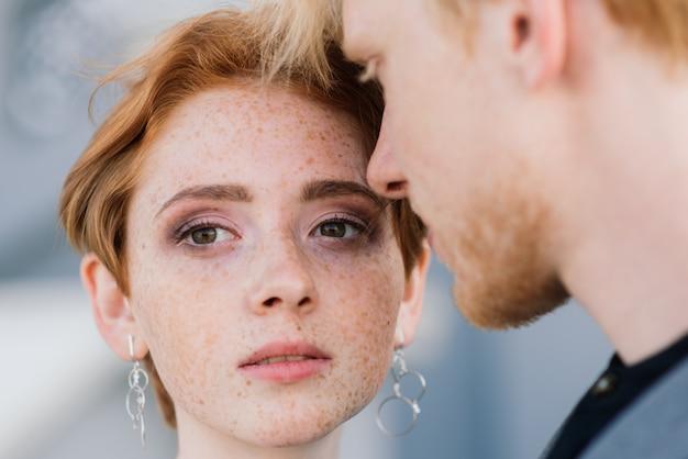 Nette rothaarige junge gerade verheiratete glückliches paar, das im sonnenuntergang draußen küsst