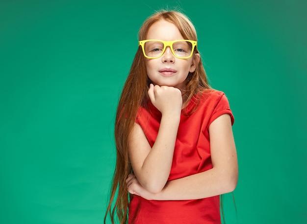 Nette rothaarige mädchengefühle gelbe brille, die grün trainiert
