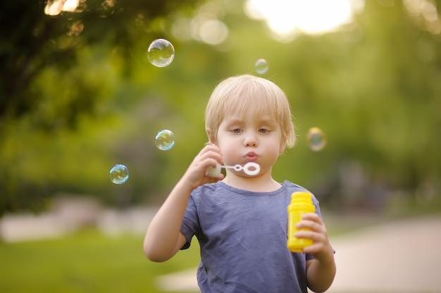 Nette schlagseifenblasen des kleinen jungen im schönen sommerpark.