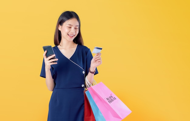 Nette schöne asiatin, die multi farbige einkaufstaschen und kreditkarte mit smartphone auf hellorange hält.