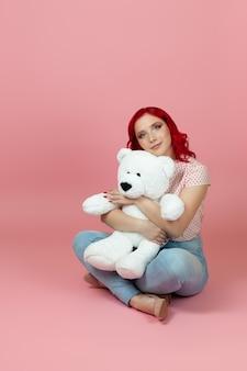 Nette, schöne frau in jeans mit roten haaren umarmt einen großen weißen teddybär, der auf dem boden sitzt
