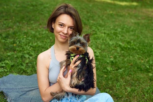 Nette schöne frau mit kleinem yorkshire terrier in einem park im freien. lebensstilporträt.