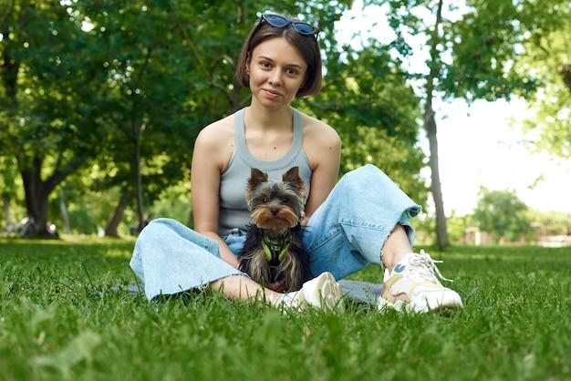 Nette schöne frau mit kleinem yorkshire terrier in einem park im freien.