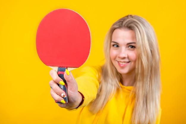 Nette schöne junge blonde frau in lässigen gelben sportlichen kleidern spielen tischtennis, hält einen ball und schläger.