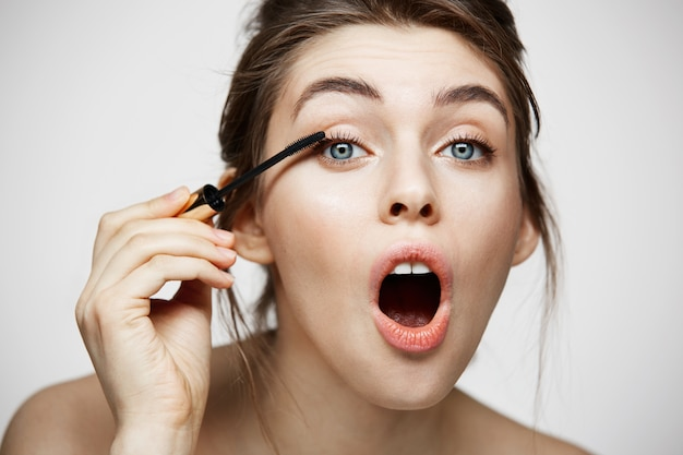 Nette schöne mädchen färben wimpern mit geöffnetem mund, der kamera über weißem hintergrund betrachtet. schönheitsgesundheits- und kosmetikkonzept.