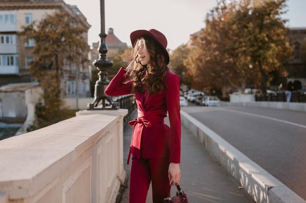 Nette schöne stilvolle frau im lila anzug, der in stadtstraße, frühlingssommer-herbstsaison-modetrend trägt hut trägt und geldbörse hält