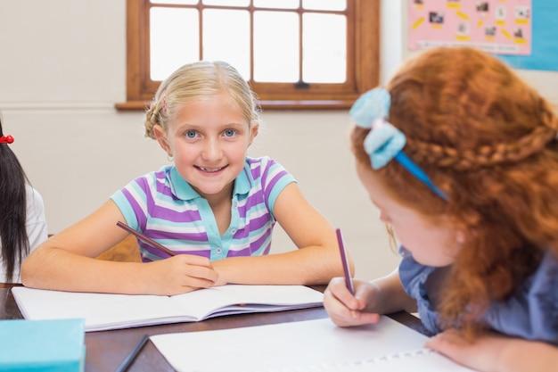 Nette schüler, die am schreibtisch in klassenzimmer schreiben