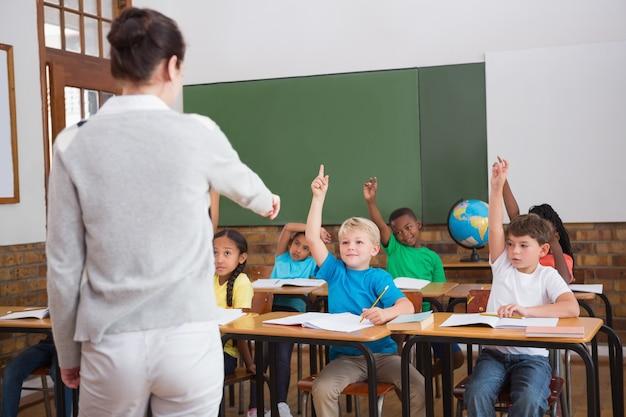 Nette schüler, die ihre hände in der klasse anheben