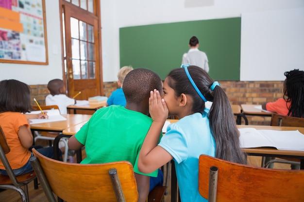 Nette schüler, die im klassenzimmer flüstern