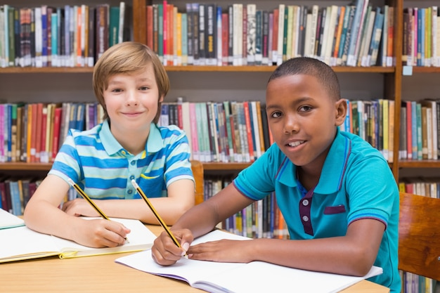 Nette schüler, die in der bibliothek zeichnen