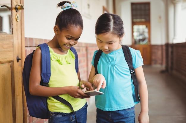 Nette schüler, die smartphone am korridor betrachten