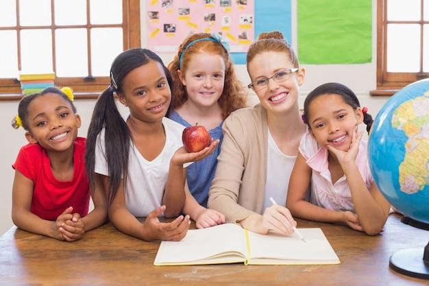 Nette schüler und lehrer, die an der kamera im klassenzimmer lächeln