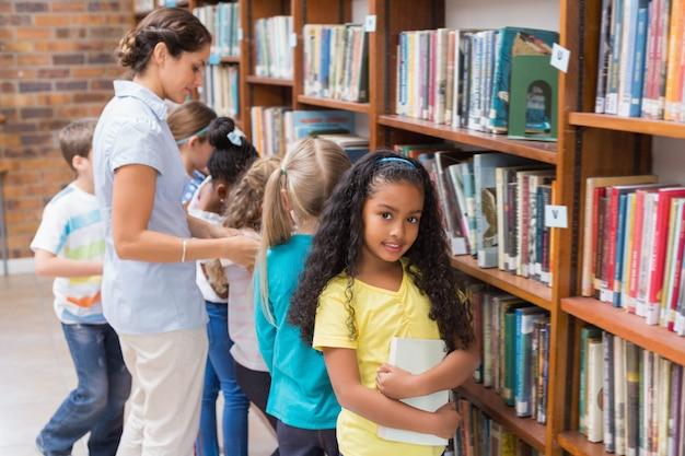 Nette schüler und lehrer, die bücher in der bibliothek suchen